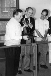 Dean Ken Davis accepts Dean's Cup trophy from School of Medicine