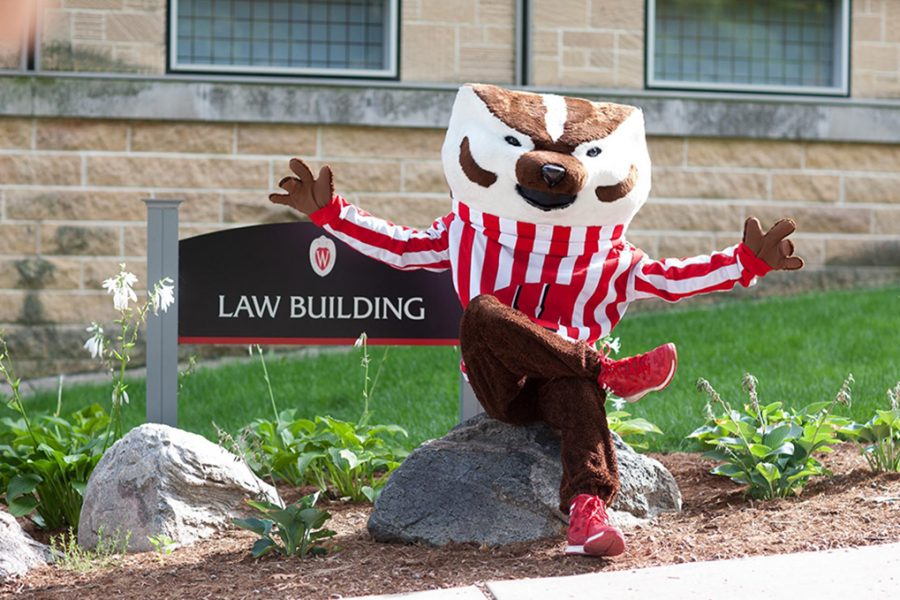 Bucky Badger sits in front of Law Building sign